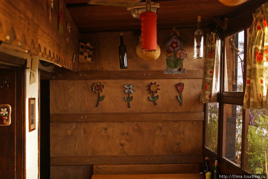 Под потолком и на стенах висят всякие штучки, картины и даже пустые бутылки.
