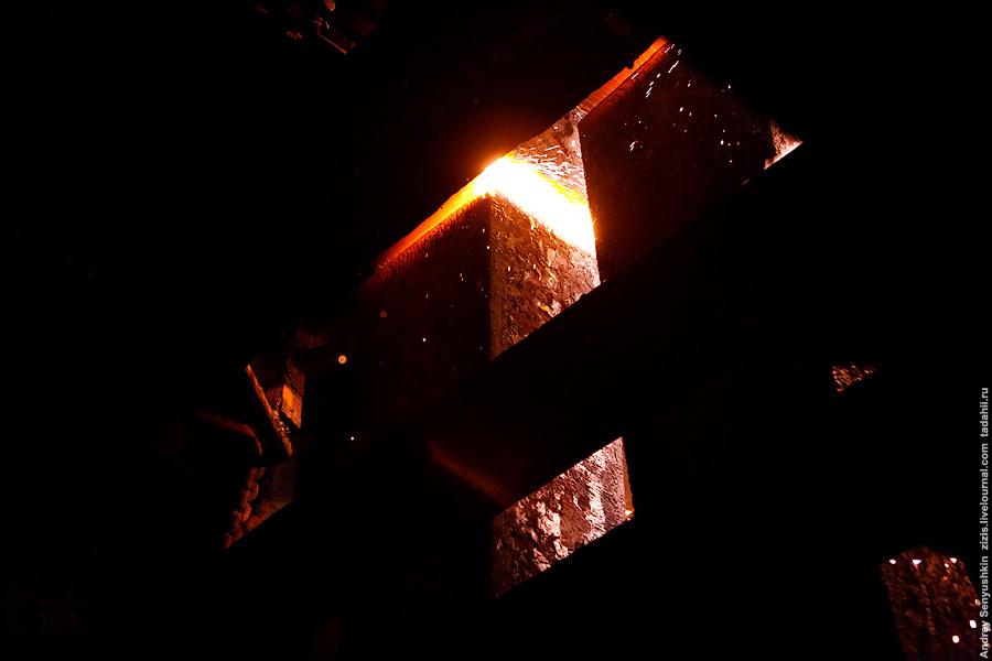 Только что отлитые огромные брусы металла, еще даже не остывшие, режутся пилами горячей резки на брусы по-меньше.