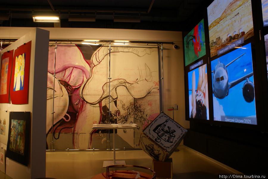 Около стены вертикально повешены три больших экрана, на которых транслируются ролики и реклама.