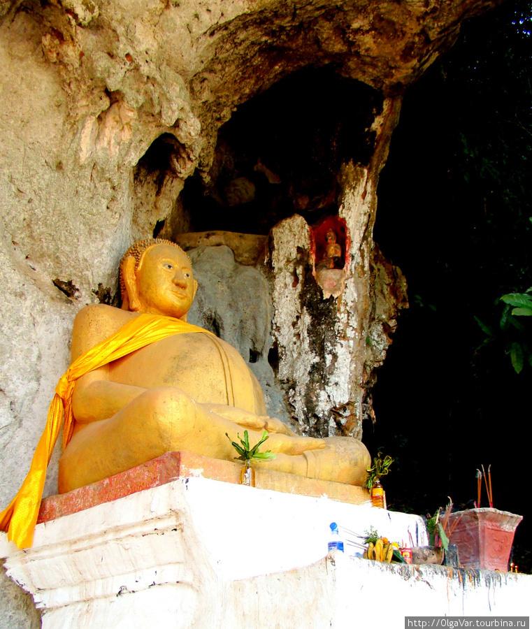 Скульптура Будды перед входом в верхнюю пещеру