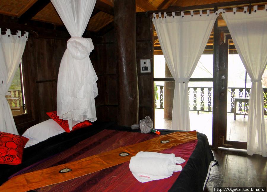 Комната просторная, особенно порадовала большая двуспальная кровать для одного человека. Но очень удивила дверь, над которой нет никакой перегородки, на открытую веранду с навесом. Потому комарам не проблема попасть внутрь комнаты.