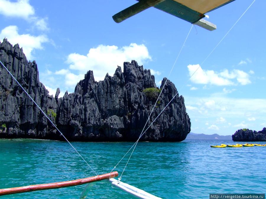 Берега острова Минилок изрезаны причудливыми скалами. Плавают привязанные каяки. Неподалеку есть пляж