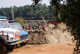 Там песок пересыпают в корзины и на головах несут к грузовикам. Грузовики, однако, на бензиновом ходу.