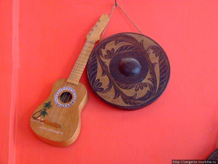 В интернет кафе на стене сувенирные муз инструменты