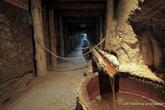 г. Величка, Польша. Соляная шахта в Величке. Поперечный штрек Кунегунда. II верхний уровень, глубина 90,7 м  Экспозиция в этой части камеры демонстрирует оригинальные деревянные желоба, предназначенные для отвода подземных утечек. В давние времена воды отводились в деревянные резервуары, т.н. кадки – одна из них виднеется вблизи лестницы. Затем вода по деревянным желобам стекала в главный резервуар, т.н. «жомпя», у шахтного ствола, откуда вытягивалась на поверхность.