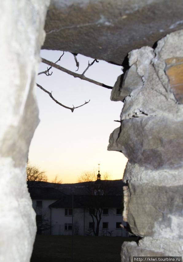 Вид на купол церкви святого Николая через бойницу замка