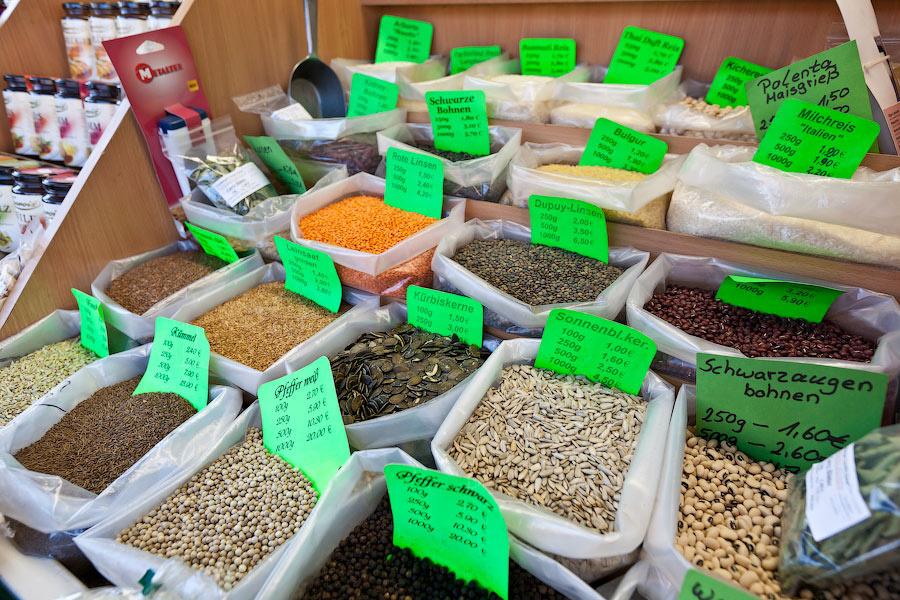 Множество мелких лотков с разными разностями. Тут продают несколько видов чечевицы, крупы, зерновые.