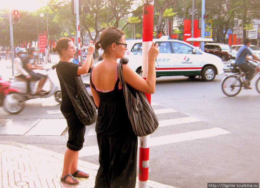 Изумленные дорожным движением туристы только успевают фотографировать