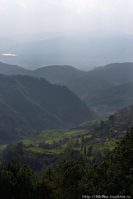 Перспектива на вершине перевала просто фантастическая, похоже что это высшая точка на сотни километров вокруг. Просматривается пространство так далеко, что, кажется, видна кривизна земной поверхности, потому что нет четкого горизонта — только десятки долин и вершин, самые удаленные из которых скрываются в голубой дымке. Это крайняя высокая отметка нашего пути по Китаю, дальше только вниз.