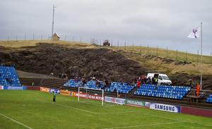 Стадион с естественным газоном вырублен в горе, на островах не найти большой ровной поляны, на склоне стоял трактор