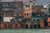 Вдоль реки много гхатов и зданий.
