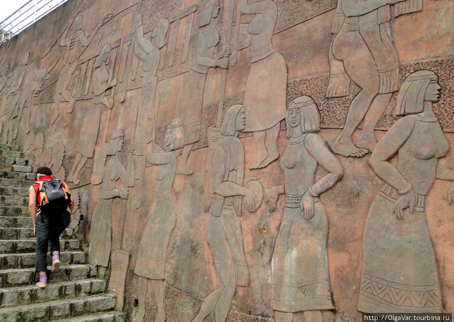 Вход на станцию канатки в городе. На стене — панно с изображениями местных горных племен латов