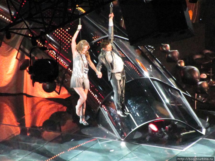 Из-под купола спускаются ведущие концерта Мари Сернехульт и Рикард Ульссун