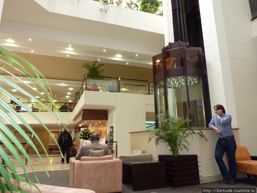 Холл гостиницы и кабина стеклянного лифта.