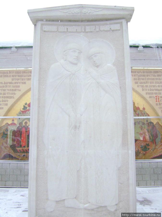 Памятник — стела святым благоверным супругам князю Петру и княгине Февронии Муромским возле монастырской стены
