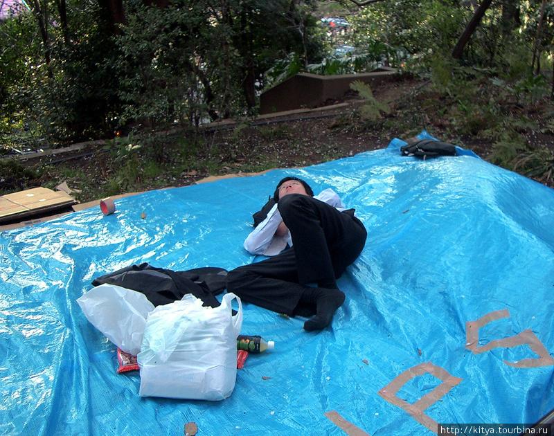 Молодой сотрудник японской фирмы занимает место под сакурами для своих коллег (парк Уэно)