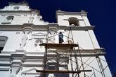 Рабочий красит фасад церкви