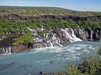 Hraunfossar рекой-то не является, он возникает прямо из горы и уже впадает множеством каскадов, растянувшихся более чем на сотню метров вдоль берега Хвалвы
