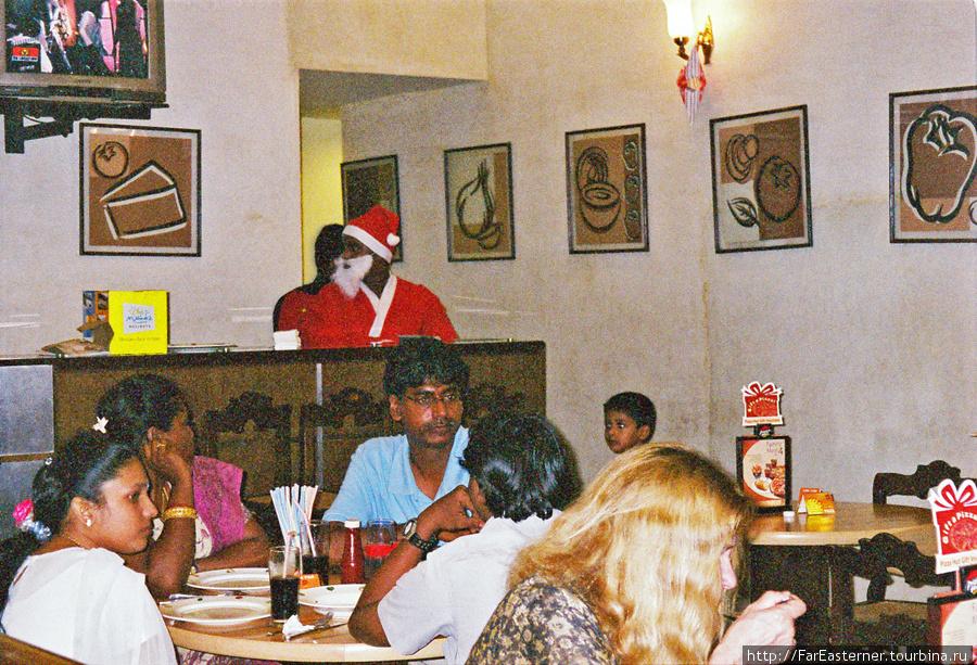 Люди обедают в Пицца Хат в Понди, штат одет как Санта Клаусы