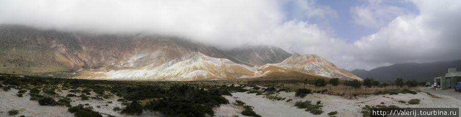 Пейзаж в желто — оранжевых тонах.  Верхушки скал вокруг кратера прикрыты облаками