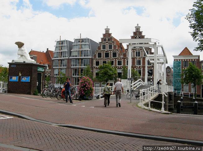 Два одинаковых домика, слева от них пристроились два современных дома — близнеца, похожих по силуэту