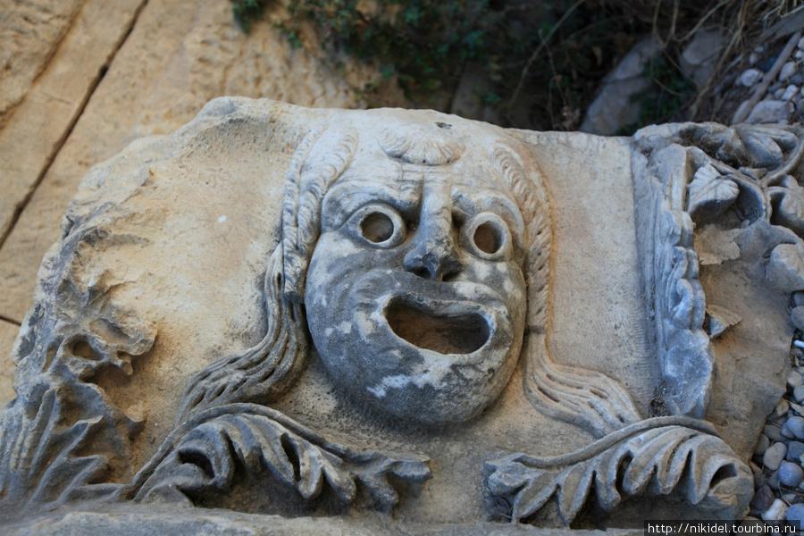 театральные маски, высеченные в камне