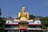 Впервые увидевшие эту гигантскую скульптуру Будды над крышей музея, между двумя башенками  в кандийском стиле, туристы считают ее частью древнего монастырского комплекса.    На самом деле, этому сооружению меньше 20 лет. Зато прообразом современным строителям при создании нового храма на нижней террасе Дамбуллы, прямо у шоссе Дамбулла — Канди служили  многие древние памятники Шри-Ланки, сосредоченные в зоне
