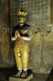 Статуя короля Канди в  храме Маха Алут Вихарая: кандийские правители даровала монастырю богатые дары, укрепляли веру — и король в традиционной одежде кандийцев (как и фигуры в росписях за его спиной) был увековечен в зале храма, у ног лежащего Будды.