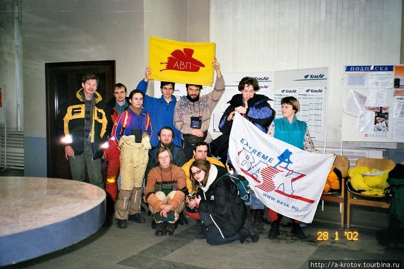 Участники зимней поездки в Туру, на месте старта — в Красноярске. Демонстрируем флаг фирмы