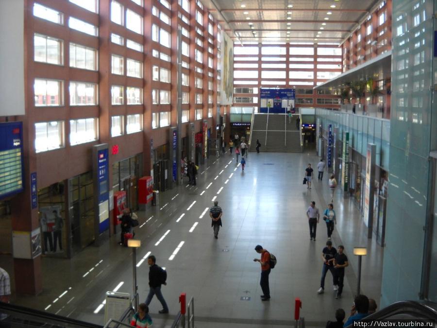 Главный холл вокзала. Сбоку слева, где синяя стойка, расположены кассы, красные билетные автоматы находятся рядом. Выход к платформам в дальней левой части зала, там же, под лестницей, есть камеры хранения
