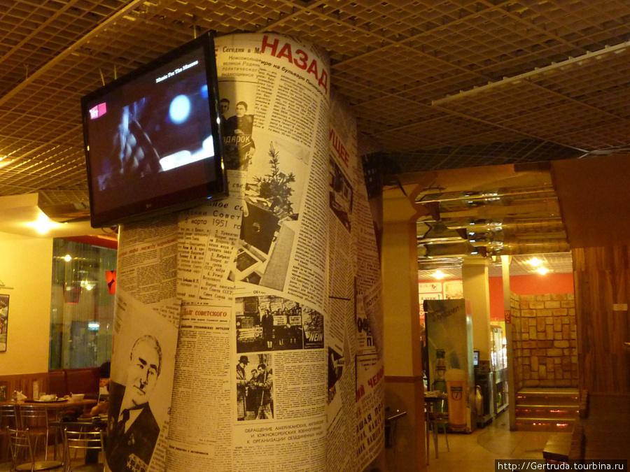 Современный телевизор на фоне старых газетных статей.