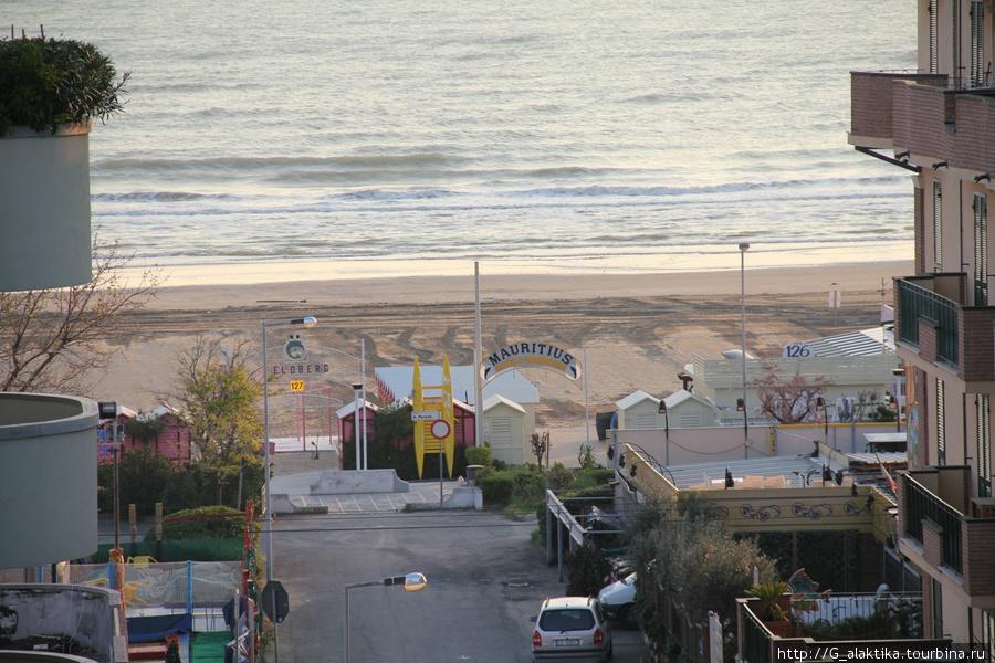 Вид с балкона на соседние отели и адриатическое побережье, розовые кабины для переодеваения переодевания  отелю.
